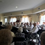 The Legacy at Clover Blossom Choir seated in two rows along the windows of our Piano Room.