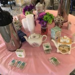 The circular table in the middle of the room: pink table cloth, flowers, tea pots, and a wide variety of tea.