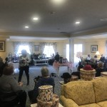 The living room, with the Women's Club spread in groups throughout, enjoying the Tea Party.
